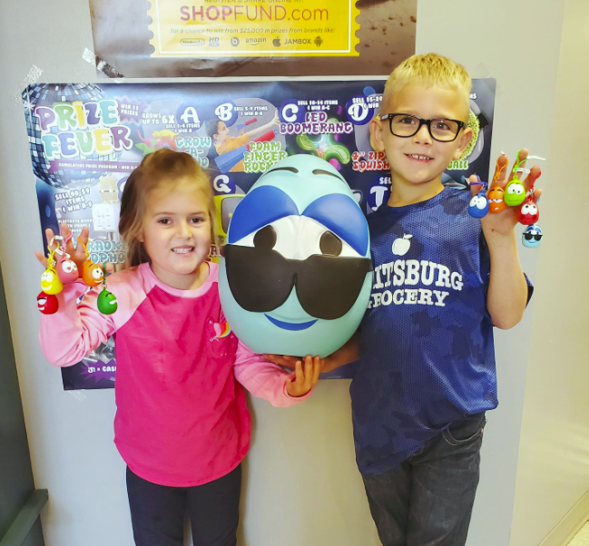 Elementary students smiling with a large Squishy